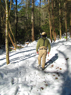 Ian walks a snowy trail along the stream in the Smokies