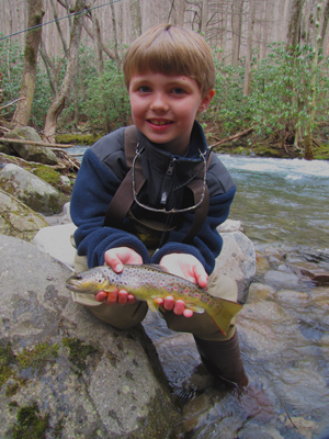 Young man shows his first trout on a fly