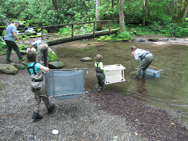 Willow & Boone help set up the mesh holding cages for the brook trout